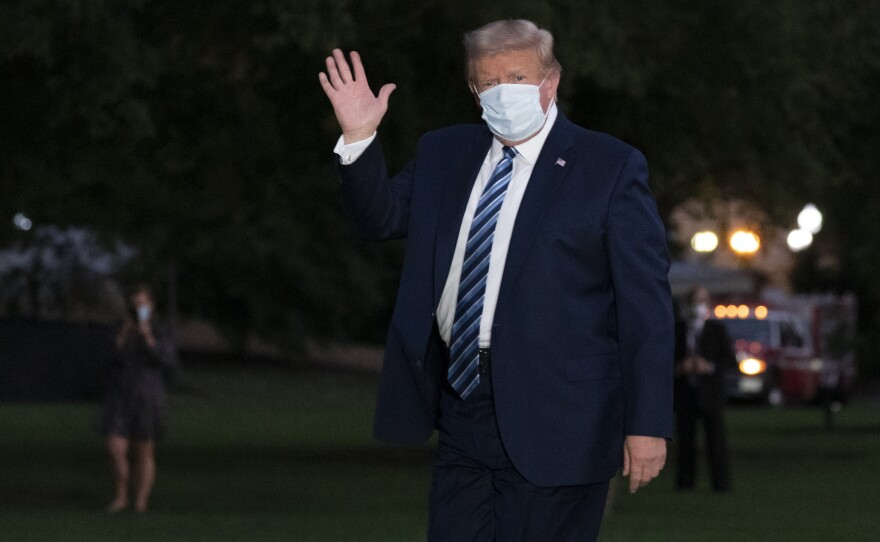 President Donald Trump waves as he returns to the White House Monday, Oct. 5, 2020, in Washington, after leaving Walter Reed National Military Medical Center.
