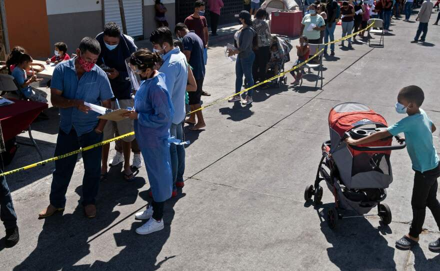 Asylum seekers camping at El Chaparral crossing port queue to be vaccinated against COVID-19 last month in Tijuana, Mexico, on the border with the U.S.