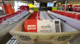 In this undated photo, unopened mail-in ballots are stacked in postal bins ready to be counted. The Postal Service says it has already handled 100 million election ballots this year.
