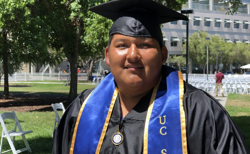 Leon Sanchez Reyes poses for a photo in his cap and gown at UC San Diego, June 15, 2018.