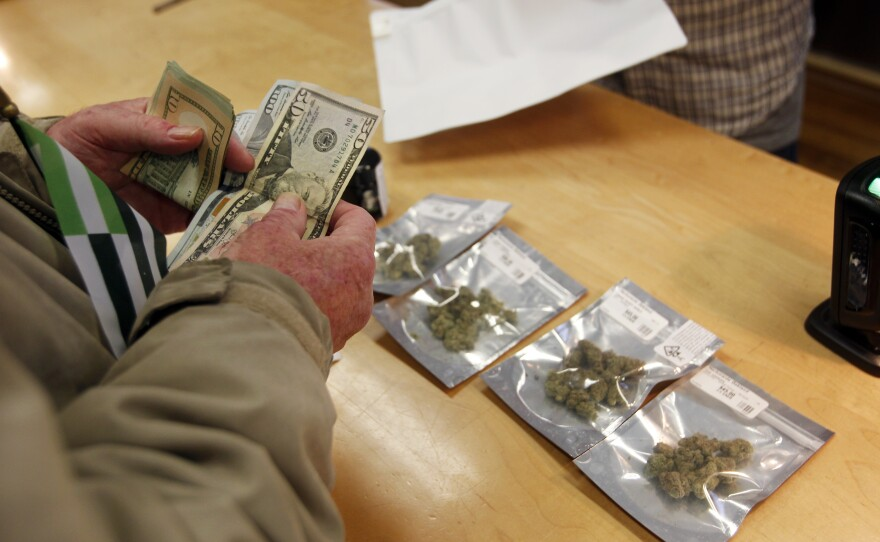 A customer purchases marijuana at Harborside marijuana dispensary, Monday, Jan. 1, 2018, in Oakland, Calif. Starting New Year's Day, recreational marijuana can be sold legally in California.