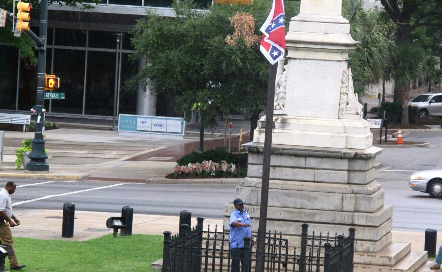 Workers raise the flag at a Confederate monument in front of the Statehouse in Columbia, S.C. Saturday, June, 27, 2015.