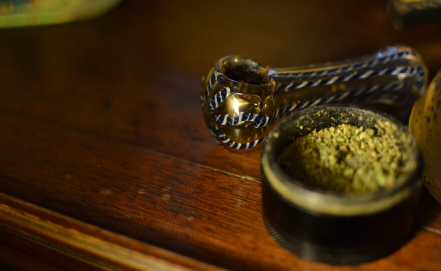 A pipe sits next a grinder full of ground marijuana, Dec. 9, 2019.