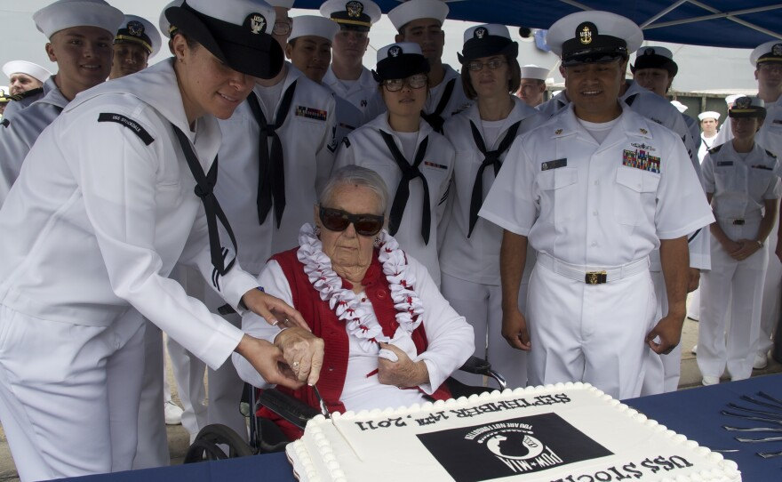 Sybil Stockdale, widow of Adm. James B. Stockdale, cuts a cake during a ceremony to commemorate POW/MIA Day at Naval Base San Diego in front of the guided-missile destroyer USS Stockdale, September, 2011.