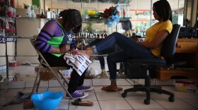 In this May 5, 2018 photo, 30-year-old Haitian migrant Marie Toussaint gives a pedicure to a customer at her local beauty salon in downtown Tijuana, Mexico. Toussaint is one of the most successful Haitian migrants in Tijuana. She opened her beauty salon with money she loaned from an uncle in Los Angeles.