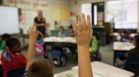 Students raise their hands while in a classroom in this undated photo.