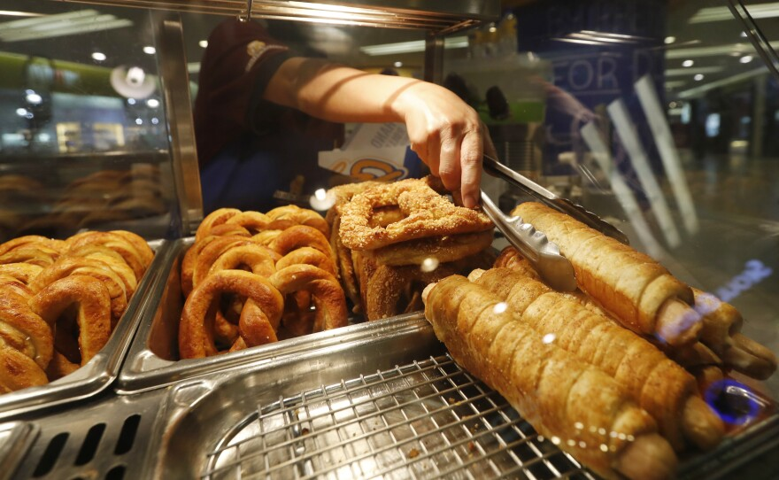 """A worker serves a """"pretzel dog"""" at Auntie Anne's at a shopping mall in Kuala Lumpur, Malaysia, on Tuesday."""