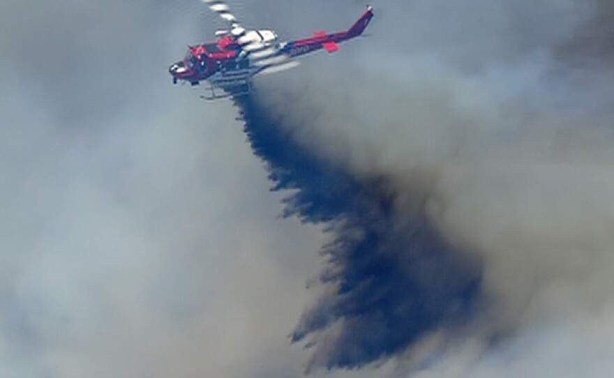 A helicopter drops retardant on a brush fire near 4S Ranch, May 13, 2014.