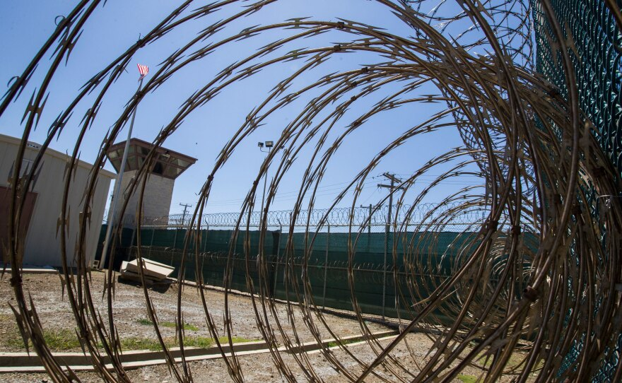 In this photo reviewed by U.S. military officials, the control tower is seen through the razor wire inside the Camp VI detention facility, Wednesday, April 17, 2019, in Guantanamo Bay Naval Base, Cuba.