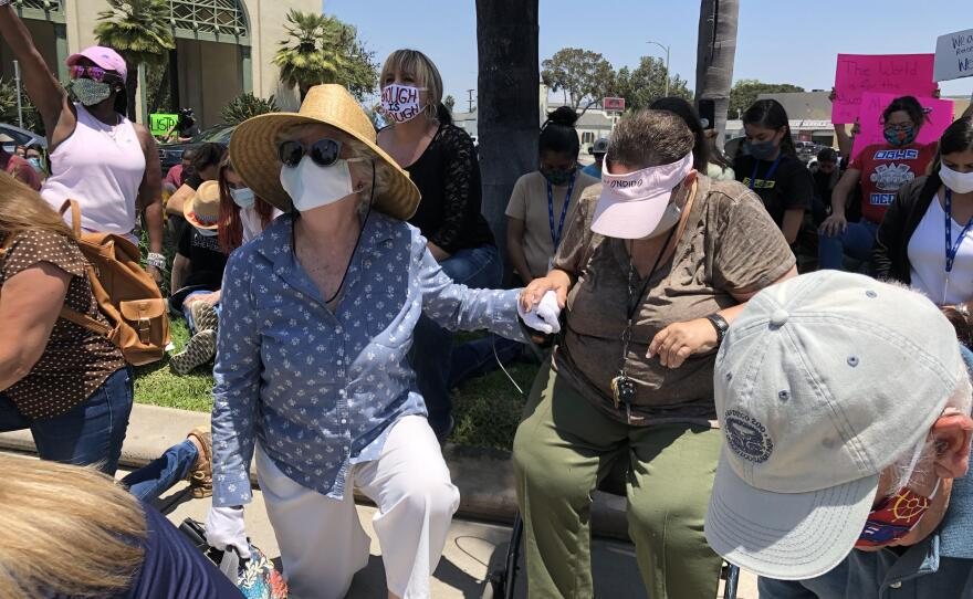 Escondido residents take a knee to protest the death of George Floyd at the hands of police, June 3, 2020.