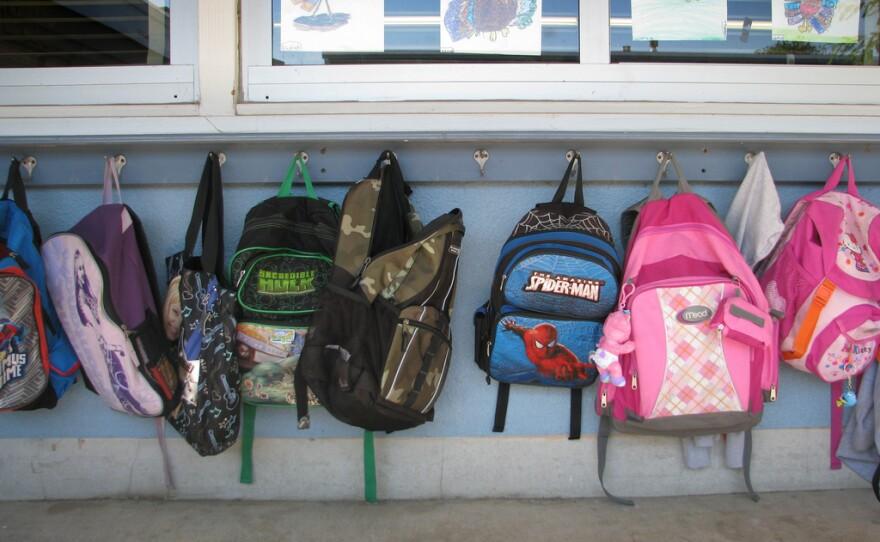 Backpacks hang outside of a San Diego classroom.