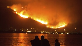 A family sits along the shore of Lake Elsinore as they watch the Holy Fire burn in the distance on Thursday night, Aug. 9, 2018.
