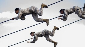 Female Marine recruits climb across ropes during the confidence building stage of their boot camp training at Camp Pendleton, March 9, 2021.