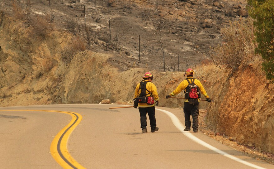 Two Cal Fire firefighters walk down a road during efforts to fight the Valley Fire in San Diego County, Sept. 8, 2020.