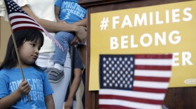 """Andrea Elena Castro, daughter of Rep. Joaquin Castro, D-Texas, holds a U.S. flag during a Rally For Our Children event on May 31 to protest the """"zero tolerance"""" immigration policy that has led to the separation of families."""