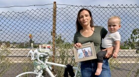 """Laura Keenan holds her son, Evan, and a picture of her her late husband, Matt, while standing next to a """"ghost bike"""" memorial where Matt was killed while biking."""