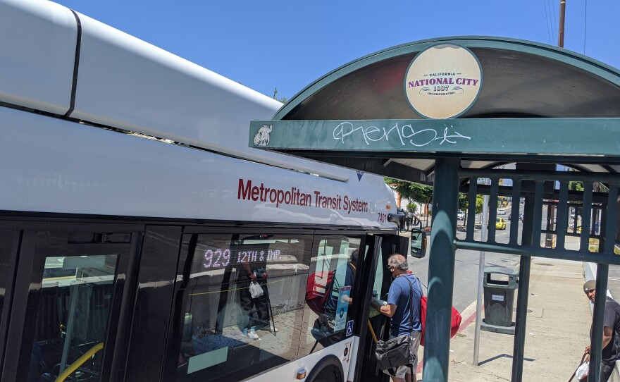 People board an MTS bus in National City, Aug. 8, 2020.