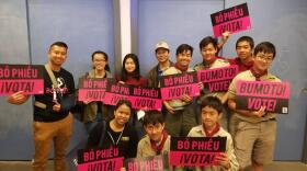 """Participants in a Viet Vote canvassing effort hold signs that say """"vote"""" in English, Spanish, Tagalog and Vietnamese, May 19, 2018."""