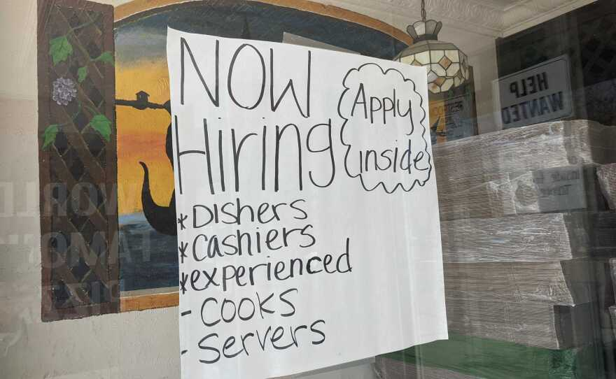 """A """"now hiring"""" sign hangs in the window of Filipe's Pizza in Escondido, Calif. Aug. 9, 2021."""