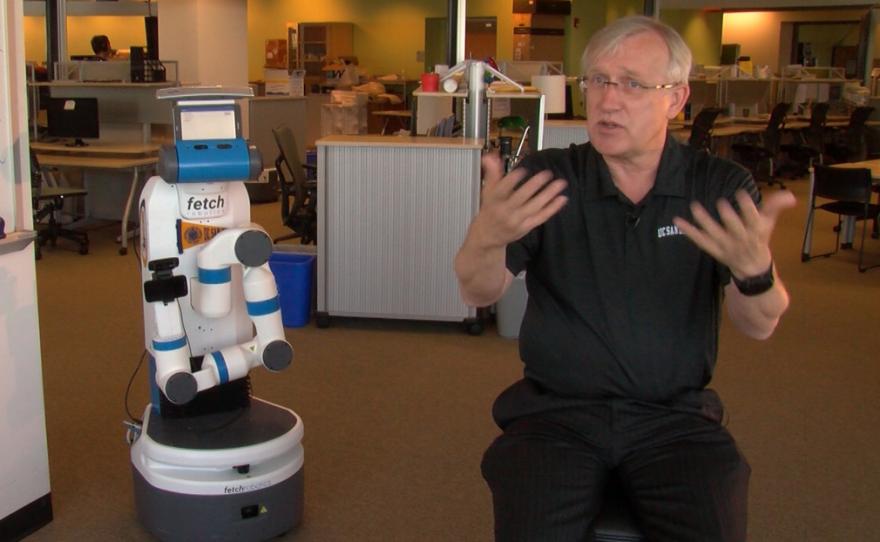 Henrik Christensen, director of robotics at UC San Diego, talks about driverless cars as robot 'Fetch' stands by.