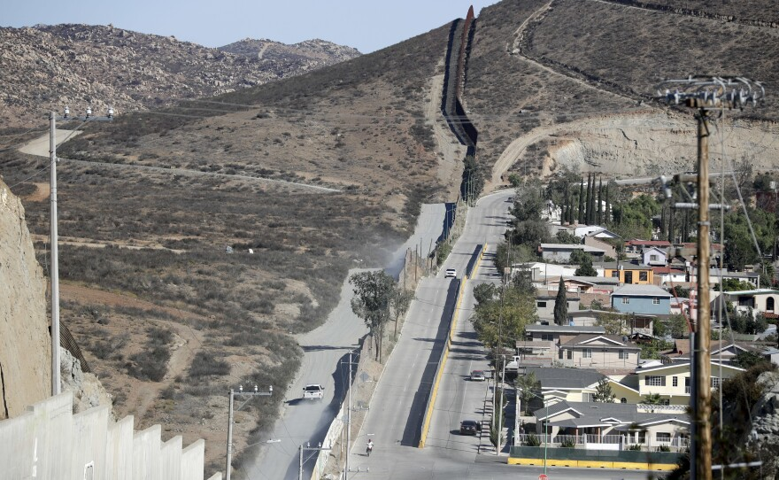 A Border Patrol vehicle drives by the border fence in Tecate, Calif., left, along the metal barrier that lines the border Wednesday, Nov. 9, 2016.