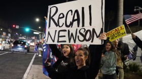 In this Nov. 21, 2020, file photo, Trump supporters shout slogans while carrying a sign calling for a recall on California Gov. Gavin Newsom during a protest against a stay-at-home order amid the COVID-19 pandemic in Huntington Beach, Calif.