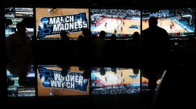 People watch coverage of the first round of the NCAA college basketball tournament at the Westgate Superbook sports book Thursday, March 15, 2018, in Las Vegas.