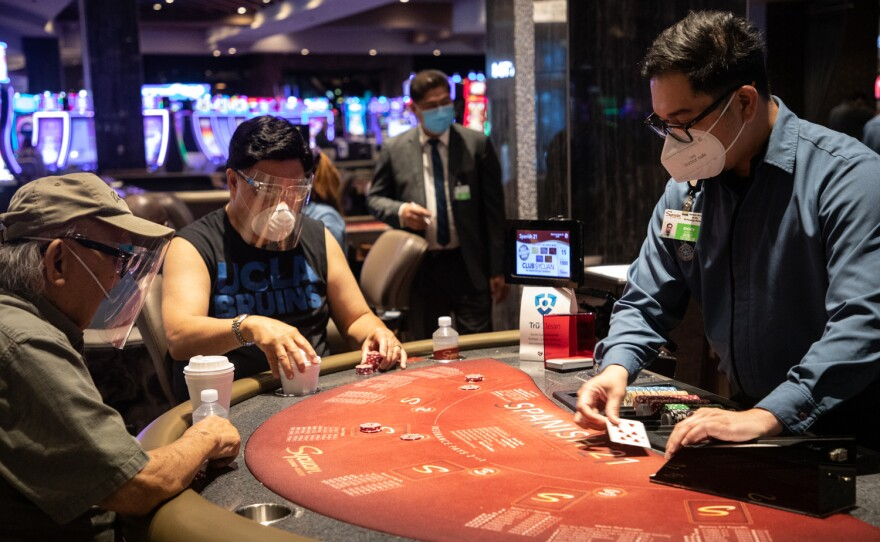 Two visitors wear face shields and masks while at a card table at the Sycuan Casino in East County, Aug. 14, 2020.