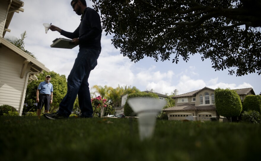 """Glen Peterson, left, looks on as Dan Denning, a water conservationist for San Diego County Water Authority checks sprinkler flow on his lawn as part of the county's """"Watersmart Checkup"""" in Carlsbad, May 6, 2015."""