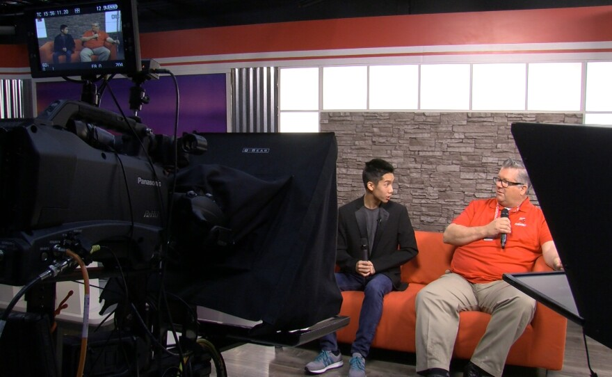 The NEST anchor Drew Dang interviews Hoover High School Principal Joe Austin on the student-run program's signature red couch, Jan. 23, 2017.