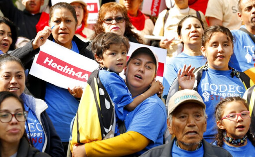 Oralia Sandoval, center, holds her son Benjamin, 6, as she participates in an Immigrants Day of Action rally,  in Sacramento, Calif. Gov., Monday, May 20, 2019.