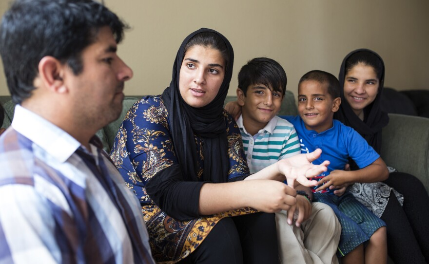 Saadia Hamdard speaks to her father Lalmir, while sitting alongside three of her siblings in her family's two-bedroom apartment in El Cajon, Aug. 1, 2017.