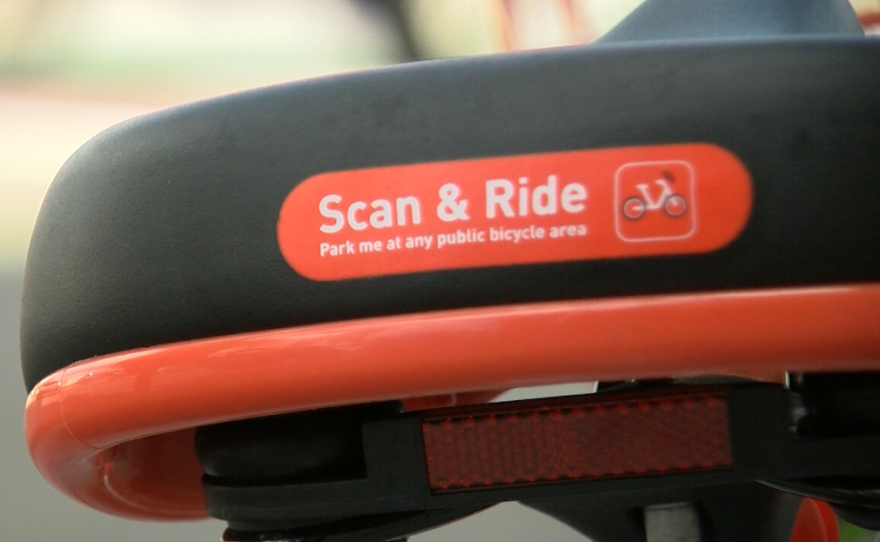 """Text on the back of a Mobike seat reads, """"Scan & Ride,"""" March 23, 2018."""