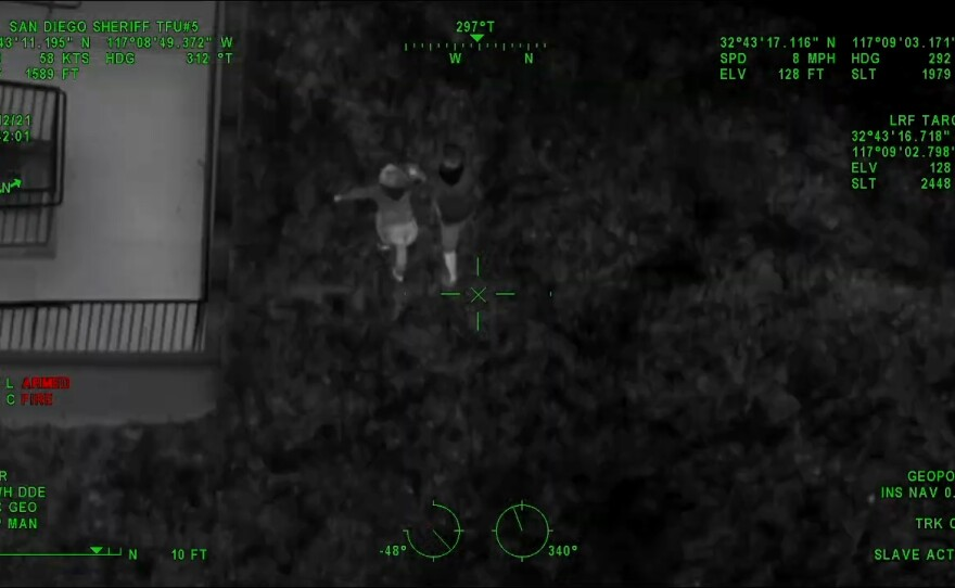 Image captured aboard a San Diego Police Department patrol helicopter showing Christopher Templo Marquez, 36, and a girlfriend Janeth Iriarte, 33, running toward San Diego High School on April 12, 2021, before an 11-hour standoff with officers that ended in a fatal shooting on April 13, 2021.