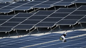 A worker helps to install solar panels onto a roof in the Van Nuys section of Los Angeles, Aug. 8, 2019.