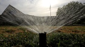 In this July 15, 2014, file photo sprinklers water a lawn in Sacramento, Calif.
