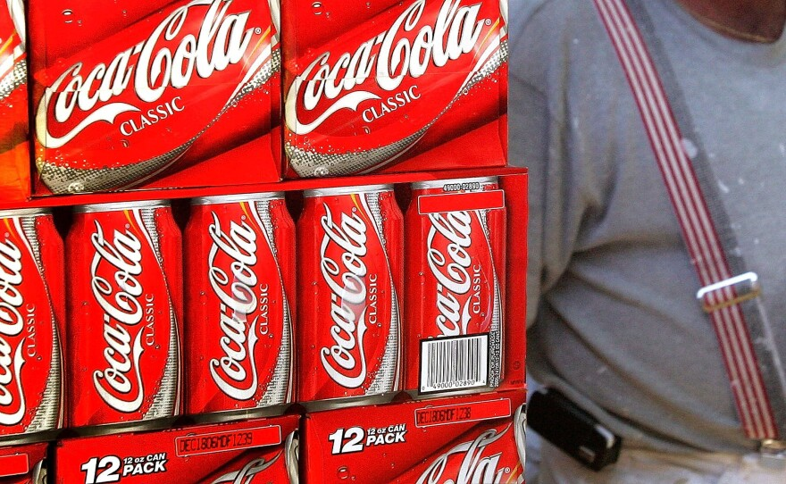 A heavyset man passes cartons of Coca-Cola displayed in a grocery store in Des Plaines, Illinois.