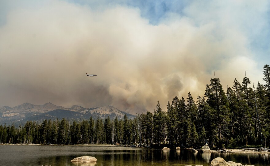 A tanker flies over Wrights Lake while battling the Caldor Fire in Eldorado National Forest, Calif., on Wednesday, Sept. 1, 2021.