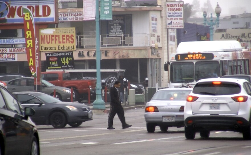 A pedestrian surrounded by cars crosses El Cajon Boulevard in City Heights, Jan. 11, 2017.