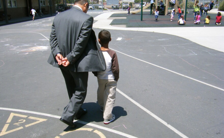 Cherokee Point Elementary School Principal Godwin Higa walks with a student on the playground in 2012.