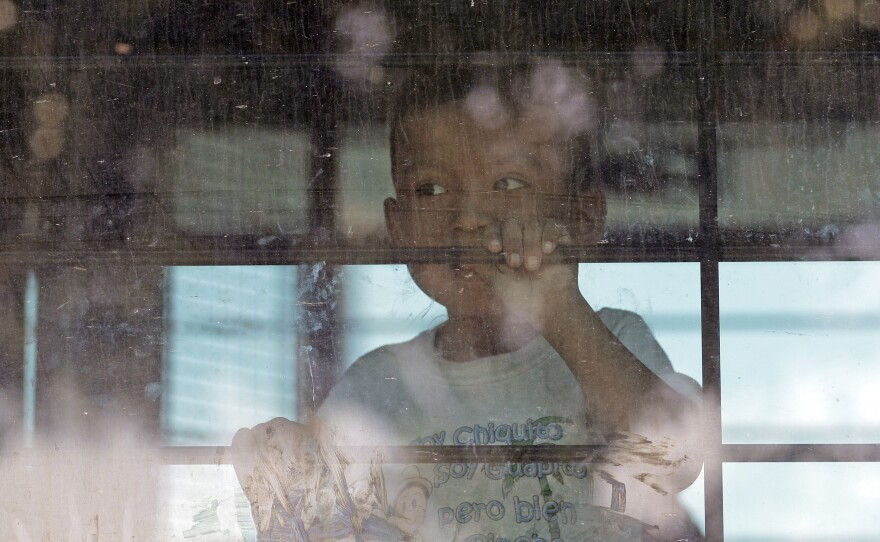 An immigrant child looks out from a U.S. Border Patrol bus leaving as protesters block the street outside the U.S. Border Patrol Central Processing Center in McAllen, Texas., June 23, 2018.