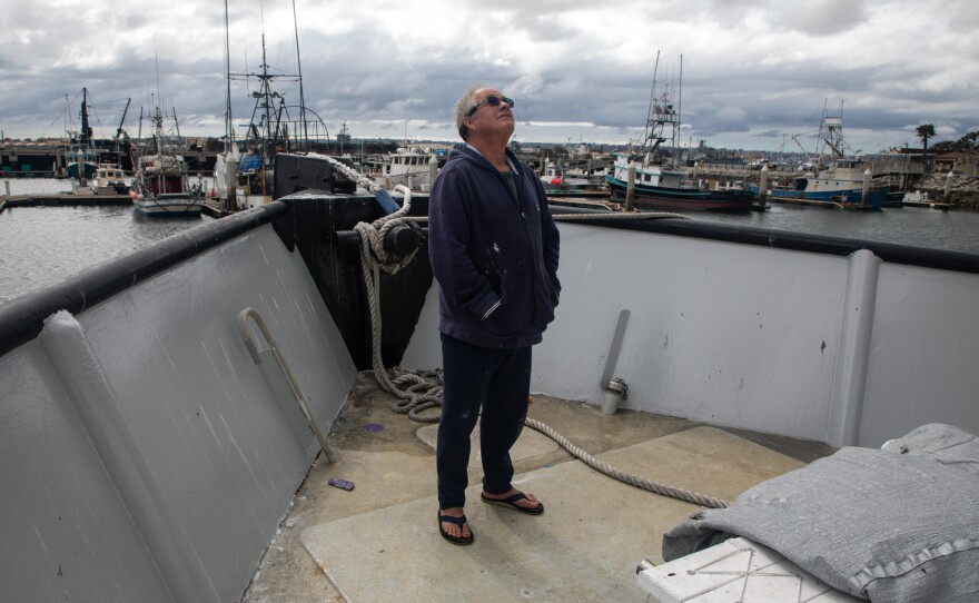 Boat owner Tim Jones surveys ongoing maintenance work from the front of his fishing boat in San Diego's Tuna Harbor, March 18, 2020. Jones will be shutting down his fishing operations as the COVID-19 outbreak continues.