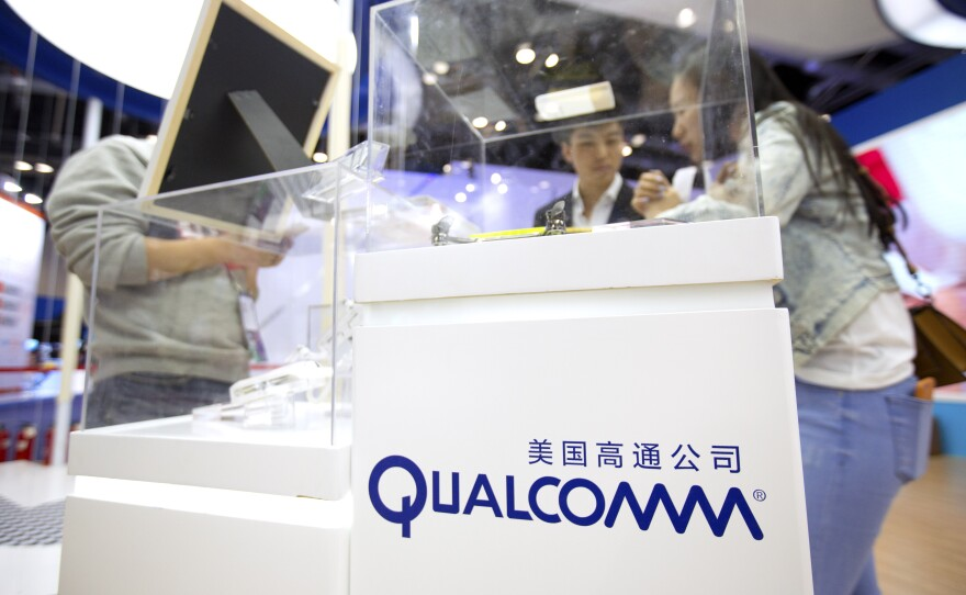 Visitors look at a display booth for Qualcomm at the Global Mobile Internet Conference (GMIC) in Beijing, Thursday, April 27, 2017.