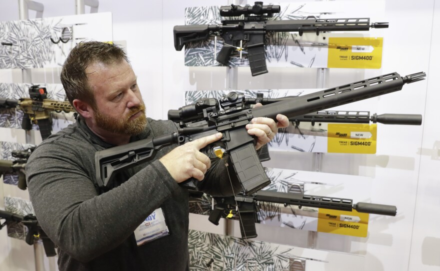 Bryan Oberc, in Munster, Ind., tries out an AR-15 from Sig Sauer in the exhibition hall at the National Rifle Association Annual Meeting in Indianapolis in 2019.
