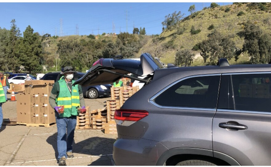 A volunteer fills the trunk of a minivan with food outside of SDCCU Stadium on March 28, 2020.