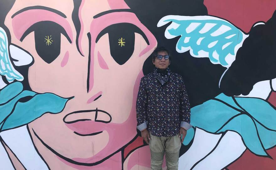The Front gallery director Francisco Morales stands in front of Fifí Martínez's mural on September 25, 2020. The work is part of a seven-artist collaboration across the border.