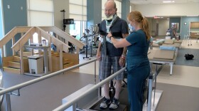 77-year-old Doug Bailey practices walking up a step inside the gym at the new Palomar Health Rehabilitation Institute in Escondido, July 15, 2021.