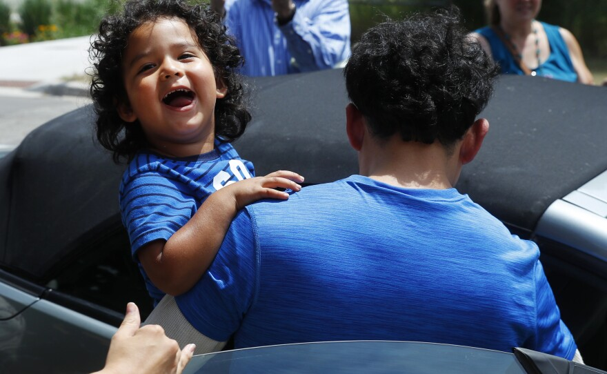 Ever Reyes Mejia, of Honduras, carries his son to a vehicle after being reunited and released by United States Immigration and Customs Enforcement in Grand Rapids, Mich., Tuesday, July 10, 2018.