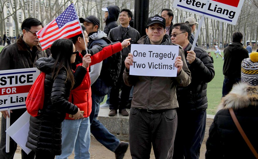 """A man holds """"One Tragedy, Two Victims"""" sign at the Feb. 20, 2016 protest in support of Peter Liang at Cadman Plaza in Brooklyn, N.Y."""