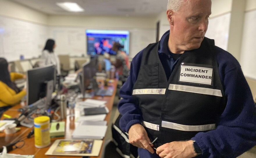 """Scripps Health president and CEO Chris Van Gorder wears a vest that says """"incident commander"""" while standing in the Scripps corporate offices, March 12, 2020."""